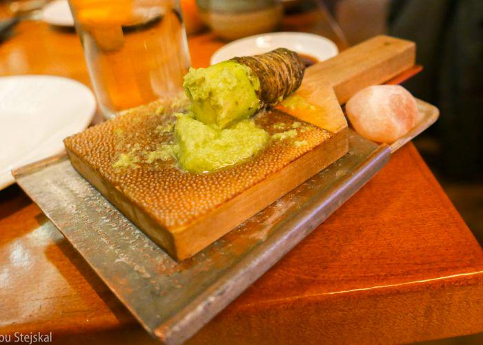 Wasabi root freshly ground by a grater on a table