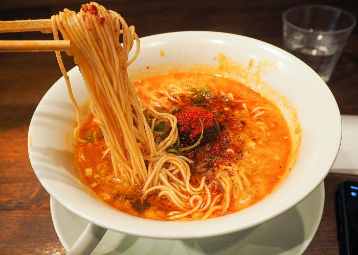 A pair of chopsticks holding noodles out of a bowl of ramen