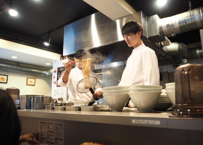 Chefs in the kitchen preparing bowls of ramen