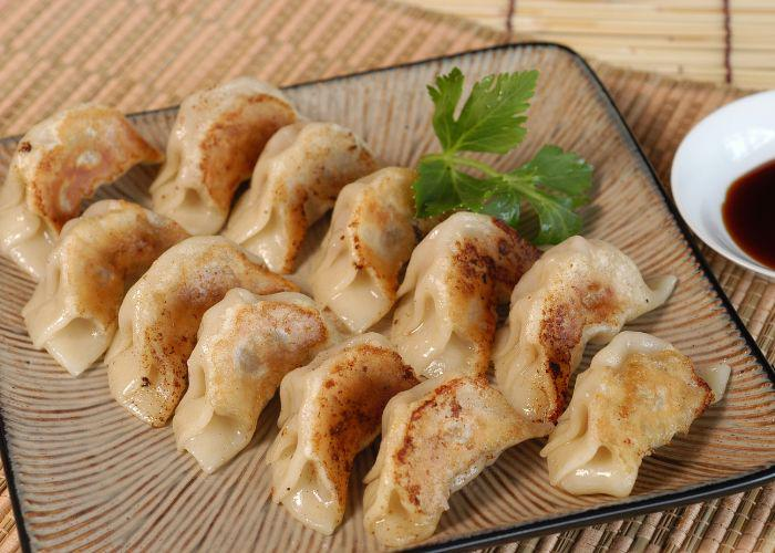 A plate with a dozen pan fried gyozas with a side of soy sauce