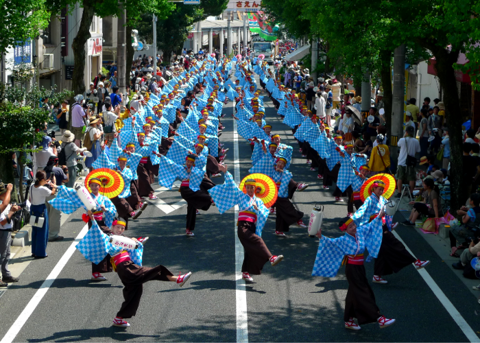 A group of people dancing traditional Japanese dance in the street in bright blue and black gowns