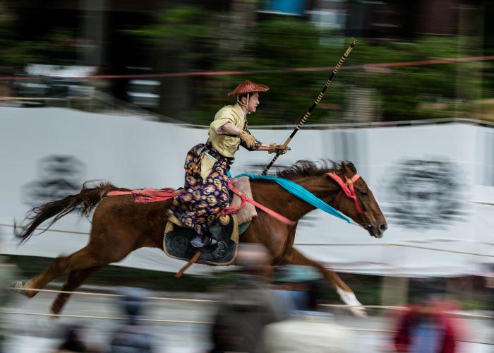 A man dressed in traditional Japanese ceremonial archery clothes riding on horseback on a brown horse