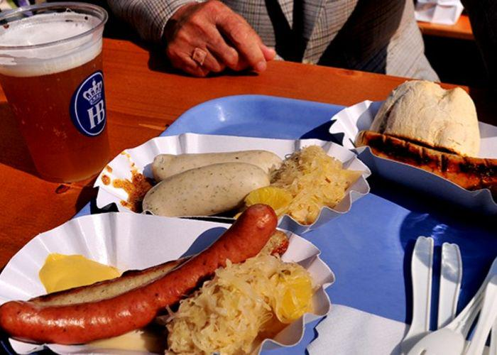 A table with a pint of beer and two buns with German sausages in and sauerkraut
