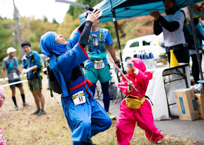 A man and child fighting dressed up as ninjas