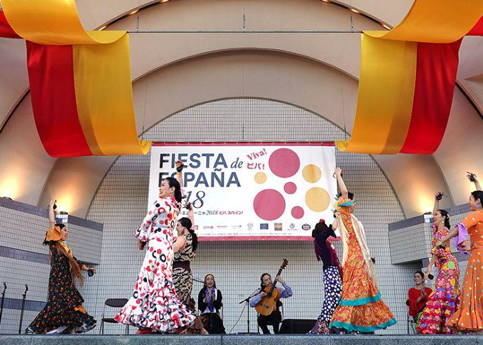 Women dancing on a stage at the Spain Fest in traditional Spanish dresses