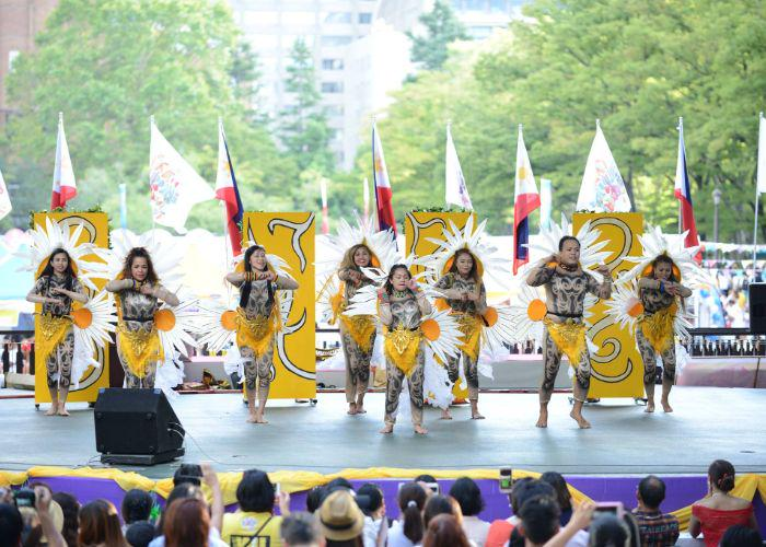 A group of performers on stage at the Philippines festival dressed in costumes with big white daisy's on