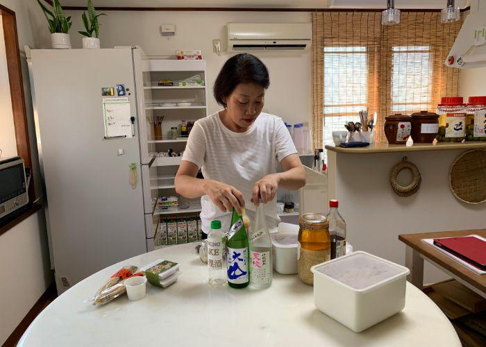 A Japanese woman stands in her kitchen behind a table laden with all manner of sake bottles, natto, miso, and other fermented foods