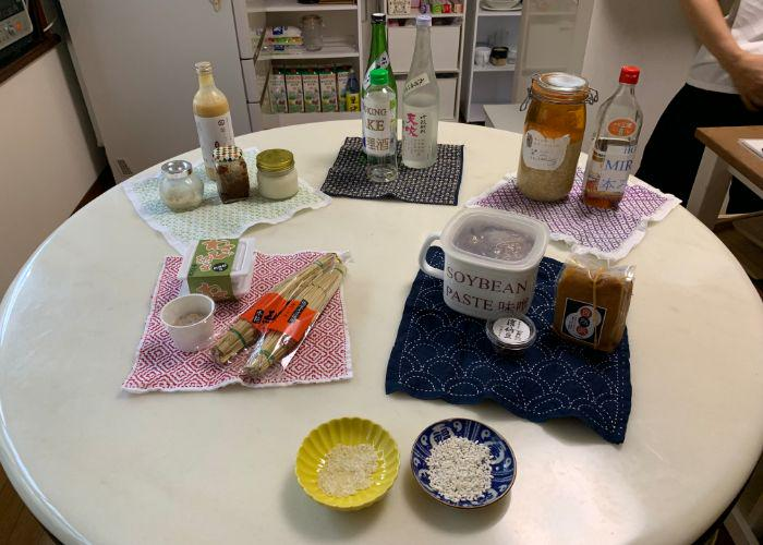 A spread of Japanese fermented food ingredients on the table, like sake, natto, miso, and koji