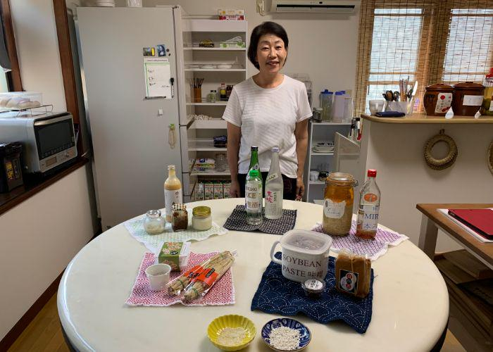 Shirley, a Japanese woman stands behind her kitchen table, smiling. There are a variety of fermented foods on the table like miso paste, soybeans, koji, sake, and natto