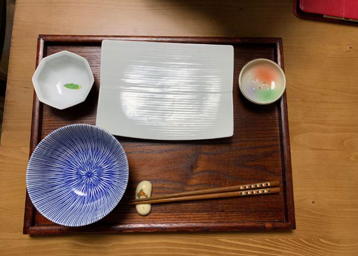 An overhead image of a wooden tray with several small dishes, a striped blue bowl, octagonal small sauce dish, chopsticks, and a rectangular white plate