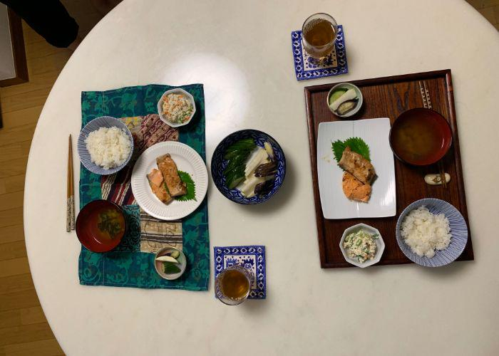 Overhead shot of a round white table with two place settings. The plates have grilled salmon, bowls of white rice, miso soup, pickled dishes, and tea