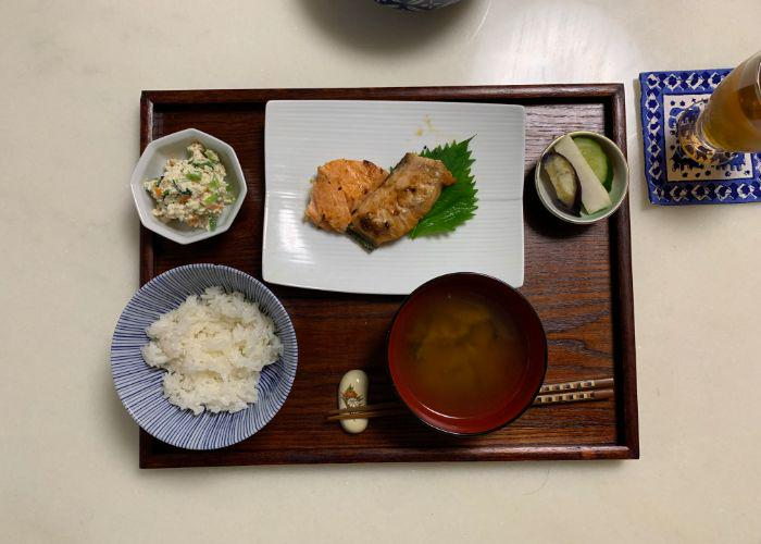 """An image of """"Ichijiu Sansai,"""" the traditional Japanese meal layout with one soup and three dishes. There is a bowl of white rice, miso soup, shiroae, Japanese pickles, and grilled salmon"""