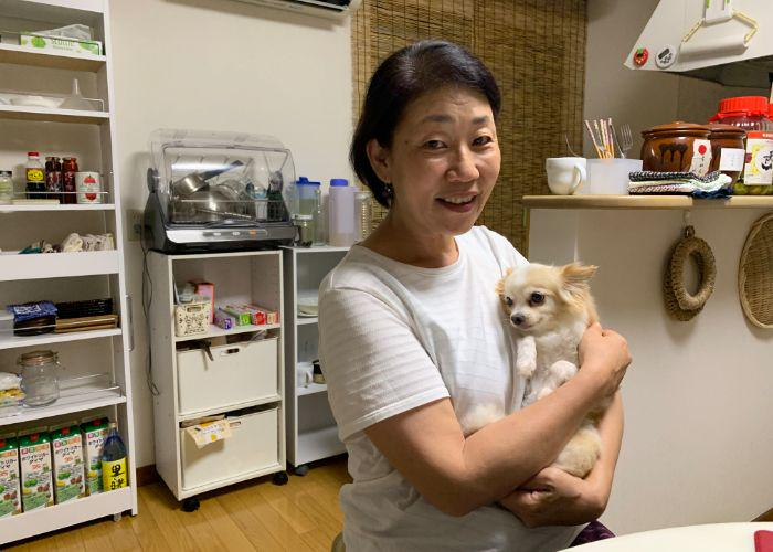 A dark-haired owman bugging her small chihuahua, Colin, in her Japanese kitchen