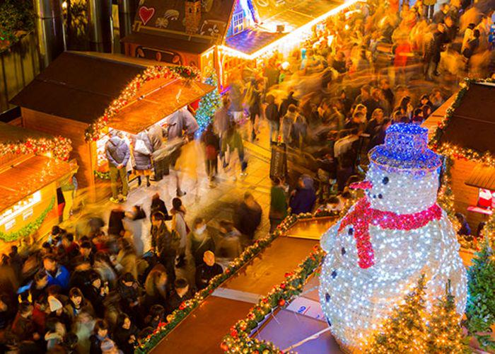 An aerial shot of the German Christmas Market in Osaka, with a large sparkling Christmas tree and crowds rushing below