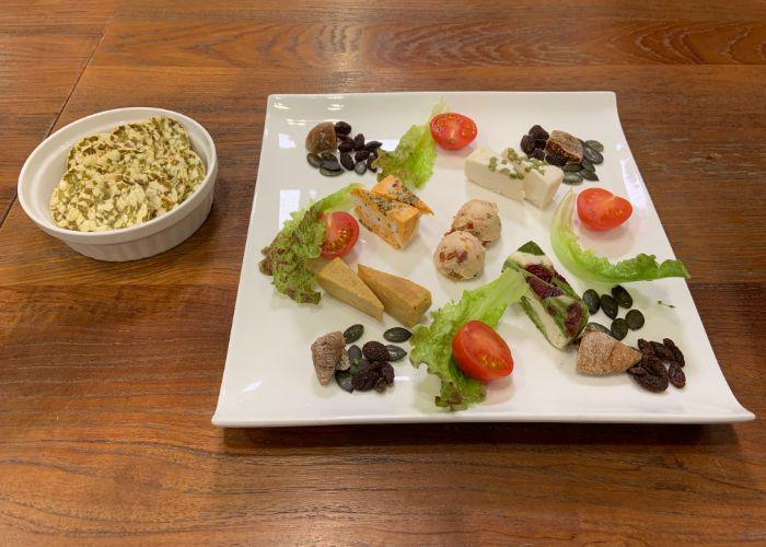 A plate of vegan cheeses that are made in-house, garnished with slices of tomato and lettuce