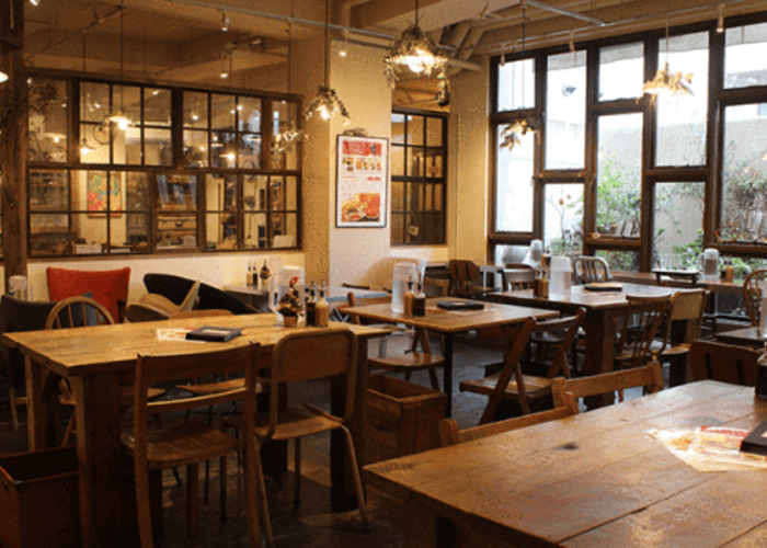 Interior of Mumokuteki Cafe, a vegan restaurant in Kyoto, with wooden tables and chairs and a very cozy atmosphere