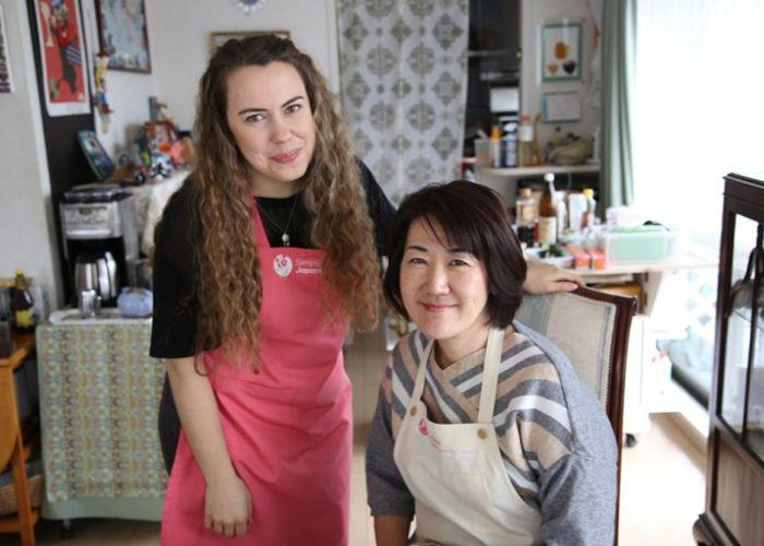 A girl with long hair in a pink apron and black shirt stands next to Miyuki Sensei, her seated cooking instructor who is also wearing a white apron in her Japanese home