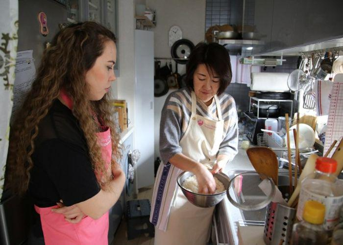 A girl in a pink apron stands and watches as her Japanese cooking instructor shows her how to wash rice