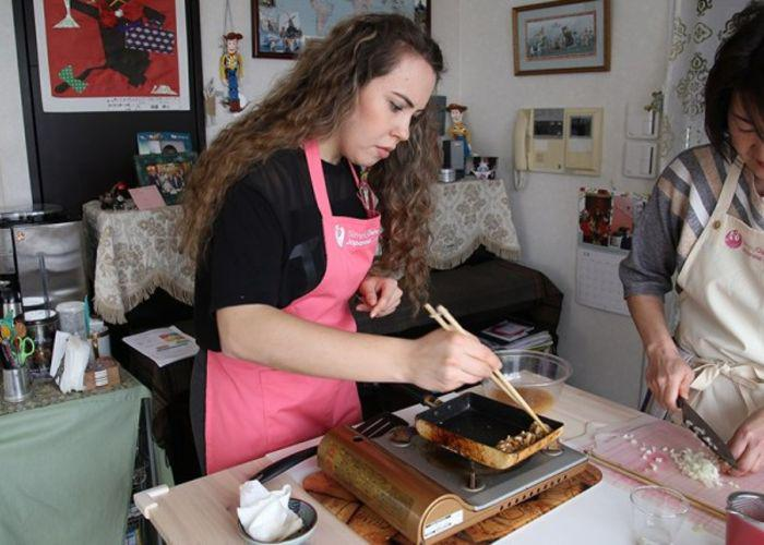 A girl in a pink apron tries to roll a tamagoyaki, Japanese omelet, as her cooking teacher looks over her shoulder