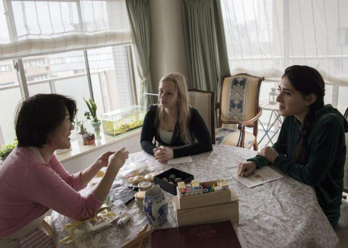 A Japanese woman shows two foreign women how to make delicious Japanese wagashi as they sit around a table together in a Japanese home