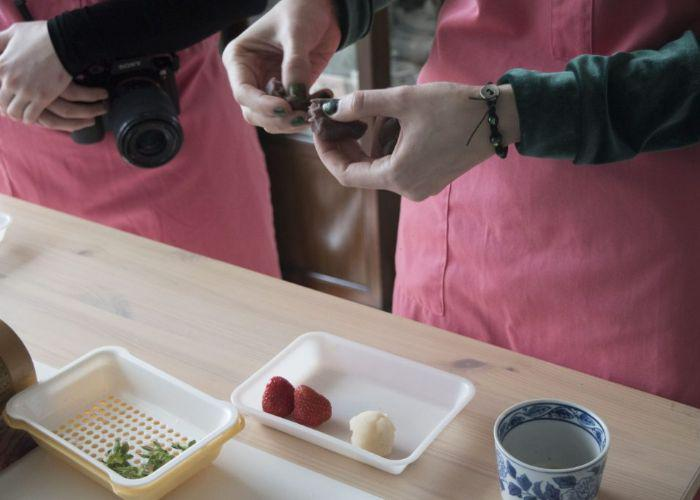 A tray of ingredients for wagashi and mochi sits on a wooden table, next to a cup of green tea