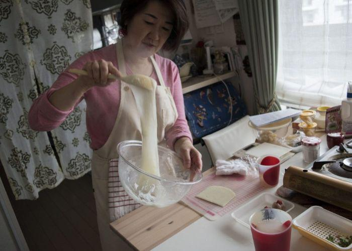 Miyuki-san, the teacher of the mochi and wagashi making class, shows how to make mochi. She is wearing an apron and stirs a sticky ball of mochi