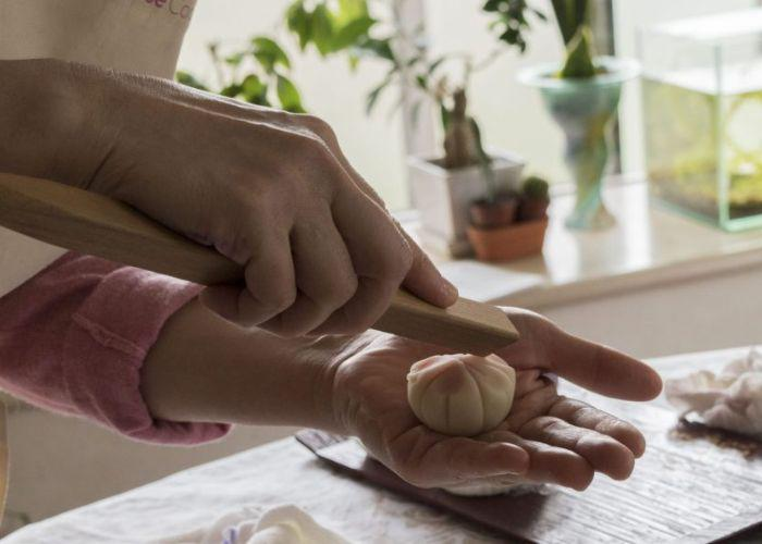 The cooking instructor holds a piece of wagashi in her hand, and uses a long wooden tool to make indents in it, creating the shape of flower petals