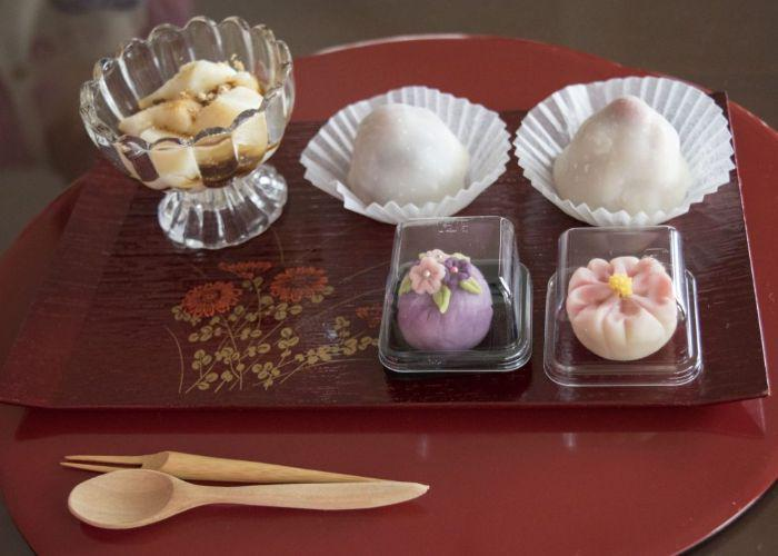 Two balls of mochi, two pices of wagashi are on a red tray with a small wooden spoon and fork.
