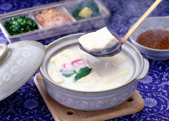 "A Japanese nabe (pot) is dipped into with a ladle, picking up a large piece of delicate white tofu, also known as ""onsen yudofu"""