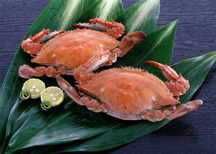 "Two boiled ""blue crabs"" (also known as Yude Takezaki Gani) sit on a bed of leaves next to green citrus halves"