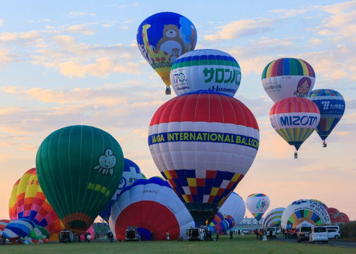 Multicolored balloons with blue, yellow, green, red, purple stripes, and cartoon characters on the float above Saga during the Saga International Balloon Fiesta.
