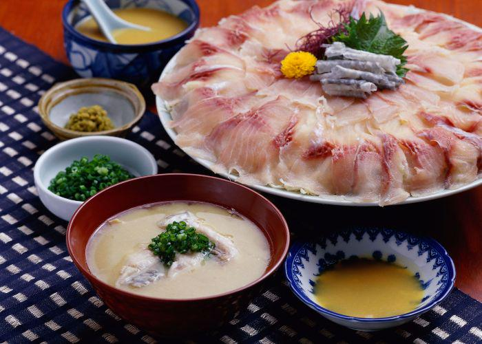 A plate of thinly sliced kankoi (koi, or carp) sashimi is laid out on a table along with miso soup, dipping sauce, chives, and other small dishes
