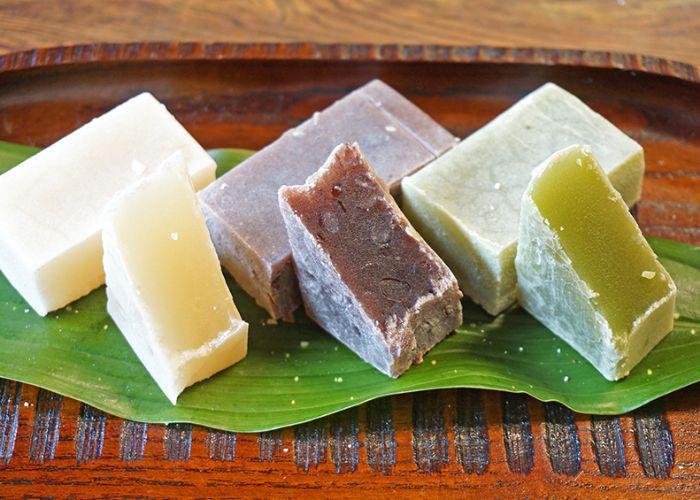 Three varieties of yokan, a Japanese bean paste-based sweet, lined up on a leaf