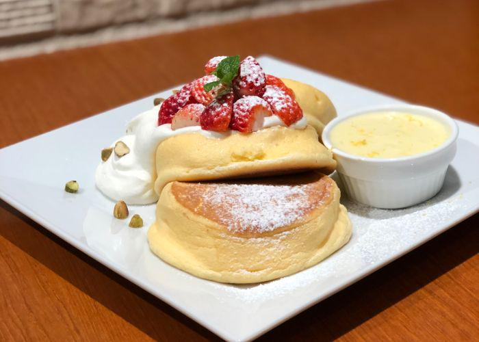Fluffy Japanese pancakes on a square plate with a dollop of whipped cream and chopped nuts