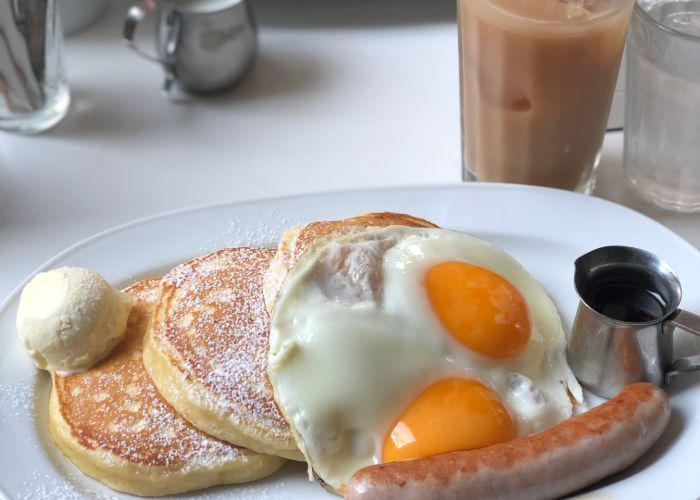 Brunch from Crisscross, including small fluffy pancakes, sunny-side up eggs, and a sausage