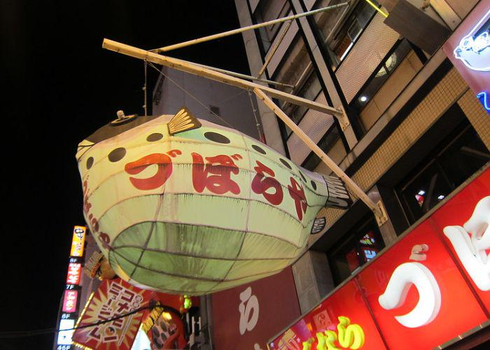 Exterior of Zuboraya (づぼらや) in Dotonbori, a well-known fugu restaurant in Osaka with a pufferfish lantern outside
