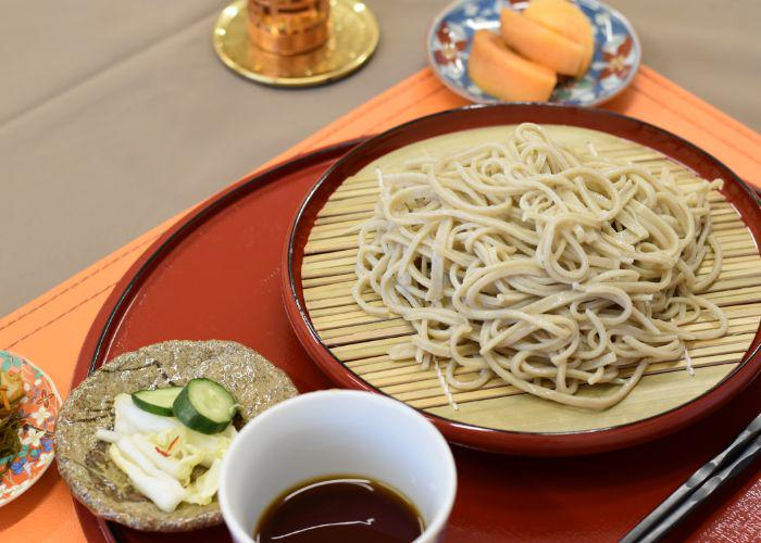 Fresh chilled soba noodles on a bamboo mat with Japanese pickles and dipping sauce