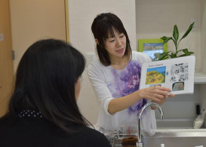 Soba cooking instructor explaining about the background and history of soba, holding an instructional book out