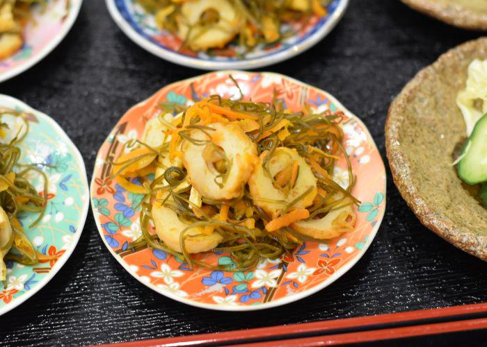 Japanese side dishes such as chilled pickles on colorful orange and blue plates