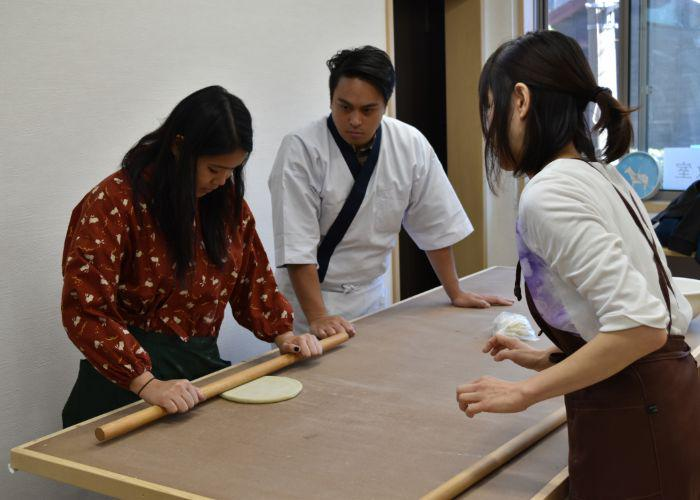 A man and a woman practice rolling out soba dough with a long wooden rolling pin