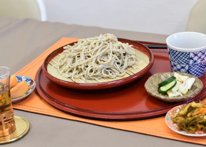 A plate of cold soba noodles, and small side dishes