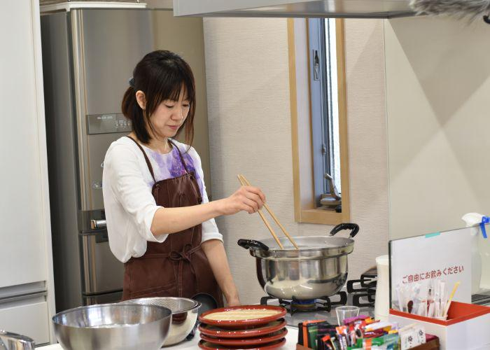 Japanese cooking instructor stands in front of the stove, stirring a boiling pot of homemade soba noodles