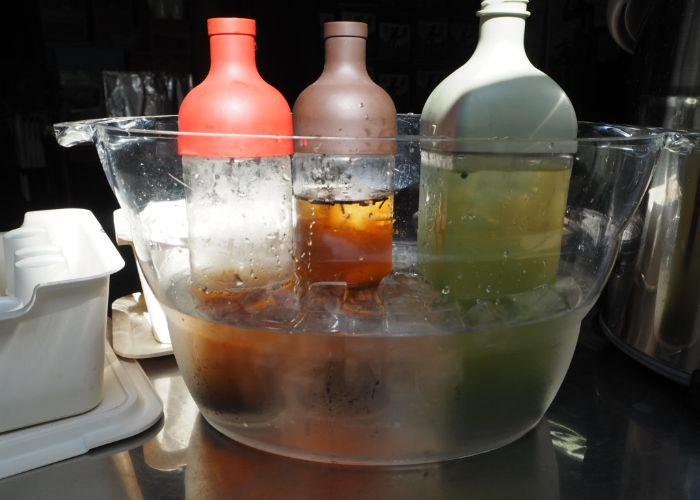 Three bottles with the three variations of tea available to drink in an ice bucket