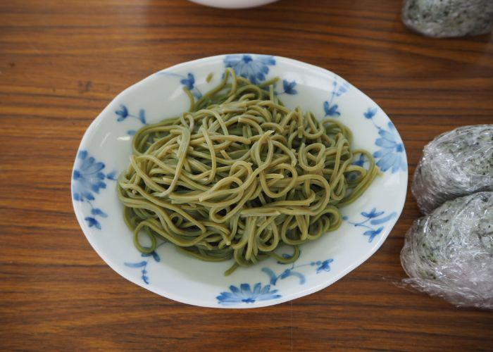 A patterned plate with green tea soba noodles and tea onigiri
