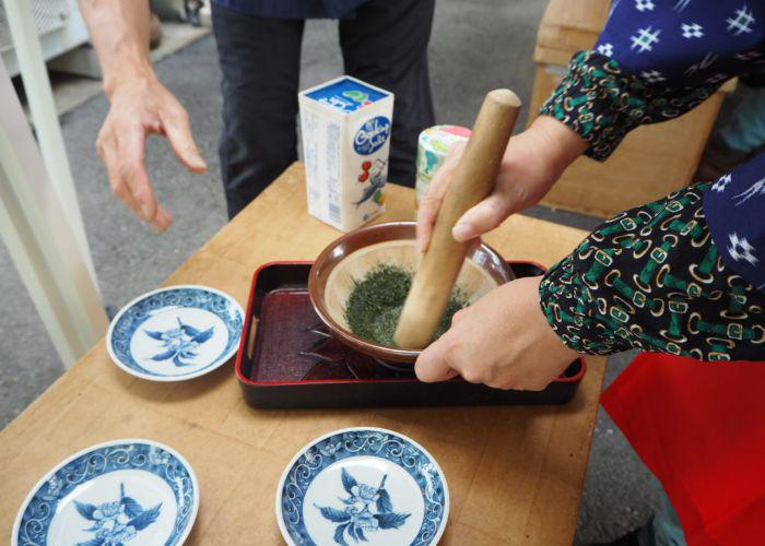 A person mixing and creating tea leaf sea salt using a pestle and mortar