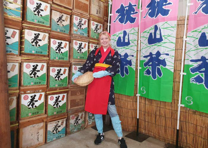 A girl wearing traditional tea picking clothes including a light cotton printed robe holding a wicker basket standing in front of boxes of tea