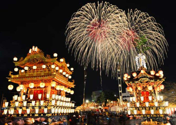 An image of two brightly decorated Japanese floats adorned in lanterns that are lit up at night with colourful fireworks exploding in the background of the night sky