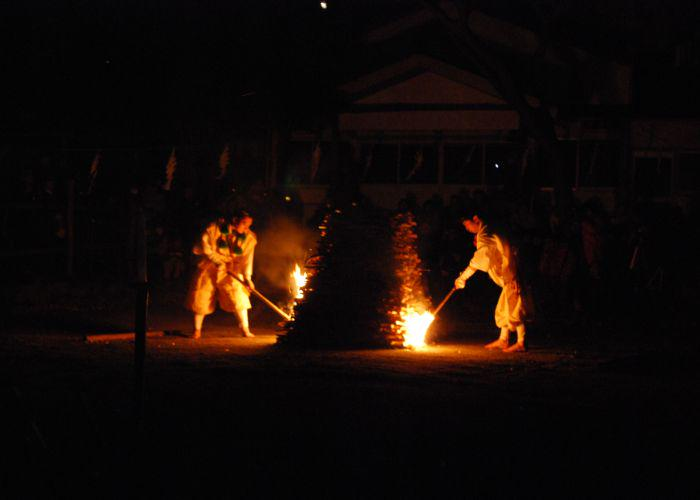Two monks dressed in white lighting a bonfire