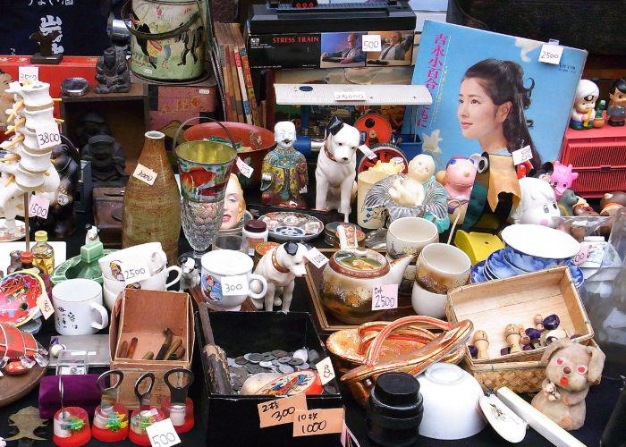 A table full of items such as mugs, plates and records at a flea market