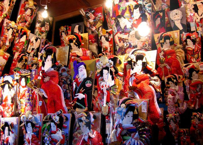 A wall full of adorned hagoita which are paddles that have Japanese people on them